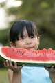 Happy little girl with watermelon in a garden - PhotoDune Item for Sale