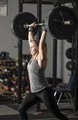 Strong female weight lifter with barbell over her head and determined look. - PhotoDune Item for Sale
