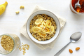 Bowl of oatmeal with banana against white table - PhotoDune Item for Sale