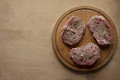Three slices of raw meat on round cutting board - PhotoDune Item for Sale