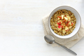 Bowl of oatmeal with apple against white table - PhotoDune Item for Sale