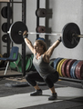 Young, strong, female weight lifter practicing snatch in weight room with heavy barbell. - PhotoDune Item for Sale