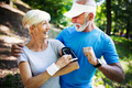 Beautiful senior couple running outside in forest - PhotoDune Item for Sale