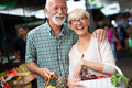 Smiling senior couple holding basket with vegetables at the market - PhotoDune Item for Sale