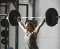 Close up of strong young woman lifting barbell over her head in gym. - PhotoDune Item for Sale