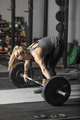 Young strong woman preparing to lift heavy barbell in gym. - PhotoDune Item for Sale