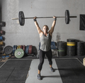 Strong young woman lifting heavy barbell over her head in a gym. - PhotoDune Item for Sale