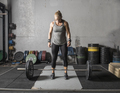 Young strong female weight lifter preparing to lift heavy barbell. - PhotoDune Item for Sale