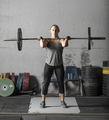 Young beautiful female power lifter lifting barbell in grungy gym. - PhotoDune Item for Sale