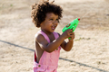 African american baby playing with water gun in the park. - PhotoDune Item for Sale