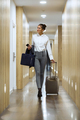 Fashionable young businesswoman walking with suitcase looking fo - PhotoDune Item for Sale
