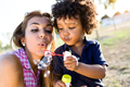 Beautiful young mother with her son blowing soap bubbles in the - PhotoDune Item for Sale