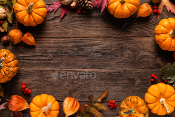 Autumn decorative pumpkins with fall leaves on wooden background. Thanksgiving or halloween holiday