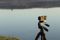 Camera on a tripod on the background of the lake. - PhotoDune Item for Sale