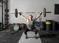 Front view of strong young woman lifting weights over her head in gym - PhotoDune Item for Sale