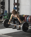 Strong female athlete preparing for heavy lift in grungy gym. - PhotoDune Item for Sale