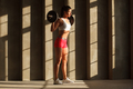 female bodybuilder with barbell on shoulders near concrete wall - PhotoDune Item for Sale