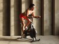 sporty female cardio training on exercise cycle in gym - PhotoDune Item for Sale