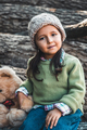 Little girl with a teddy bear sitting on logs - PhotoDune Item for Sale