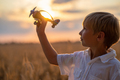 Boy in a  white shirt with a plane in hands against sky. Kid hol - PhotoDune Item for Sale