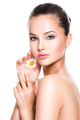 Face of young beautiful woman with singl camomile in hand - PhotoDune Item for Sale