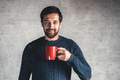Dark-haired guy holds a red cup in his hand on a gray background - PhotoDune Item for Sale