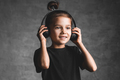 Little girl wearing headphones standing isolated on grey wall listening to music - PhotoDune Item for Sale