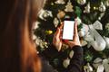 hand holding smart phone mobile near christmas tree - PhotoDune Item for Sale