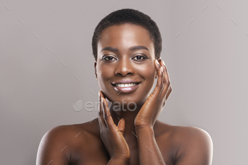 Beautiful black woman with short hair touching her smooth cheeks