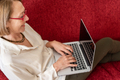 Elegant mature woman using computer at home - PhotoDune Item for Sale