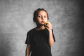 Portrait of a happiness little girl eating a green apple on gray background. Health, wholesome food - PhotoDune Item for Sale