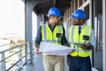 Architects discussing plan at construction site - PhotoDune Item for Sale