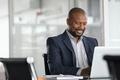 Black mature businessman working on laptop - PhotoDune Item for Sale