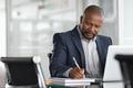 Mature businessman writing on documents - PhotoDune Item for Sale