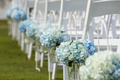 Bouquets of hydrangeas hanging from chairs for outdoor wedding. - PhotoDune Item for Sale
