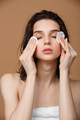 Woman cleaning her face with lotion and cotton pads - PhotoDune Item for Sale