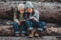 Two little girls reading books, sitting on a log. ?oncept of education and friendship - PhotoDune Item for Sale