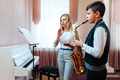 teacher claps  for a student on saxophone in music lesson that focuses on playing - PhotoDune Item for Sale