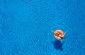 Aerial view of a woman in red bikini lying on a donut in the pool - PhotoDune Item for Sale