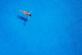 View from the top as a woman in a red swimsuit lying on her back in the pool. Relaxing concept - PhotoDune Item for Sale