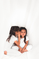 Cute little girl whispering something to her sister under the cover - PhotoDune Item for Sale
