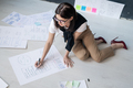 Young female broker in smart casual sitting on the floor and drawing diagrams - PhotoDune Item for Sale