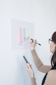 Young female broker making presentation of financial paper chart on whiteboard - PhotoDune Item for Sale
