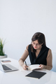 Young successful businesswoman writing down plan of working day by desk - PhotoDune Item for Sale