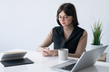 Businesswoman scrolling in smartphone while having drink at break in office - PhotoDune Item for Sale