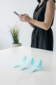 Row of blue paper charts on desk on background of businesswoman with smartphone - PhotoDune Item for Sale