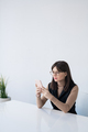 Pretty young businesswoman in smart casual scrolling in smartphone by desk - PhotoDune Item for Sale