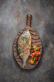 Fried whole Sea bream fish with vegetables on cutting board, copy space - PhotoDune Item for Sale
