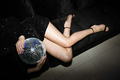 Slim legs of young woman in black glittering mini dress holding disco ball - PhotoDune Item for Sale