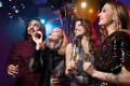 Glamorous girl blowing soap bubbles among friends with flutes of champagne - PhotoDune Item for Sale